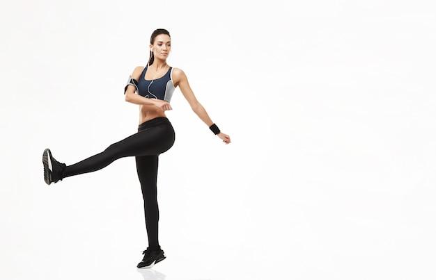 Mulher de esporte fitness em fones de ouvido, aquecendo o treinamento em branco.
