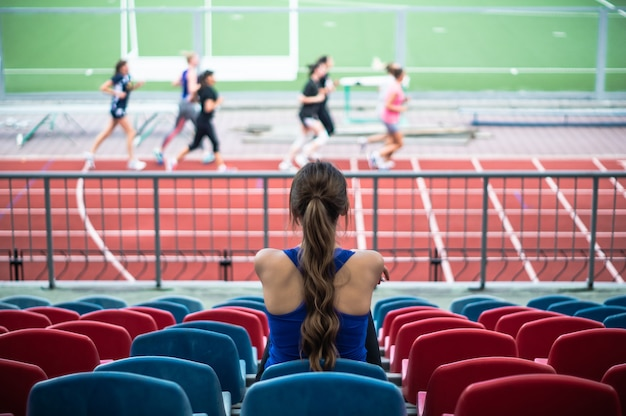 Mulher de esporte fitness em moda sportswear, senta-se olhando para a mulher de esporte em execução, exercício de fitness no estádio. conceito de estilo de vida saudável.