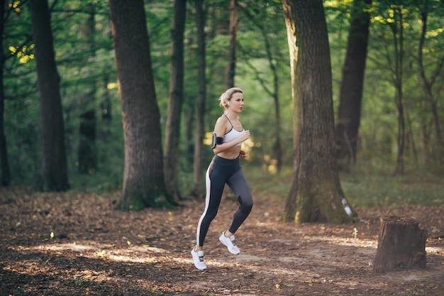 Mulher de esporte fitness jovem correndo na estrada da floresta de manhã