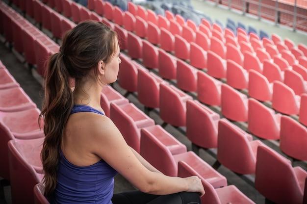 Mulher de esporte fitness na moda sportswear, senta-se olhando para a mulher de esportes em execução, exercício de fitness no estádio. conceito de estilo de vida saudável.