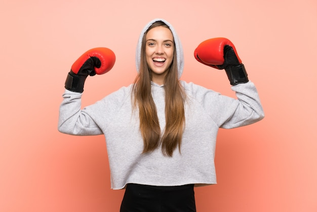 Mulher de esporte jovem feliz rosa com luvas de boxe