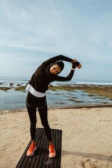Mulher de esporte muçulmano na praia exercitando