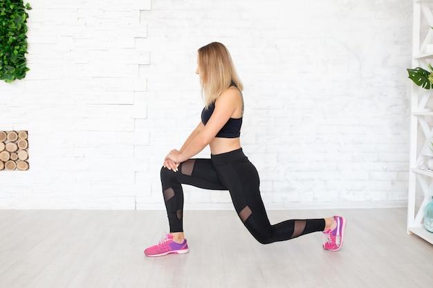 Mulher de esporte no chão, fazendo o exercício em roupas com estilo de esporte
