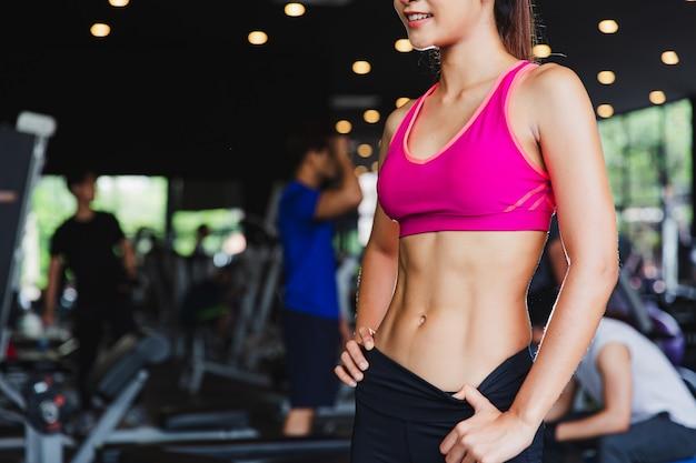 Mulher de esporte olhando seu corpo e descansando após o treino ou exercício no ginásio de fitness funcional. treino de treino para corpo construir aptidão malhar e conceito saudável de ioga