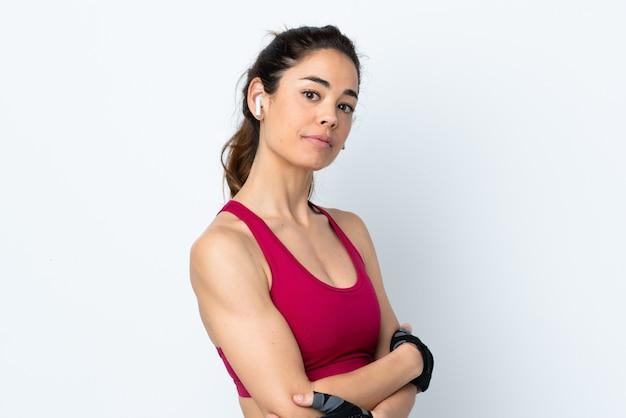 Mulher de esporte sobre branco isolado, mantendo os braços cruzados