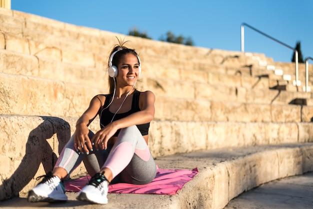 Mulher de esportes ao ar livre em uma escada descansando depois de fazer música exercício