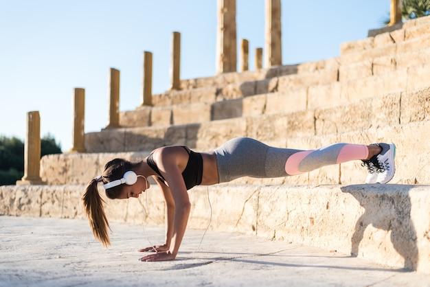 Mulher de esportes ao ar livre em uma escada fazendo música exercício
