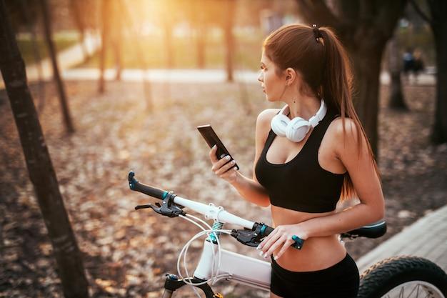 Mulher de esportes com fones de ouvido fica com telefone e olha para longe perto de uma bicicleta ao pôr do sol no parque