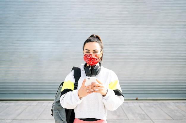 Mulher de esportes com máscara ouvindo música com fones de ouvido e smartphone