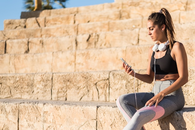 Mulher de esportes descansando e ouvindo música usando seu telefone celular nas escadas