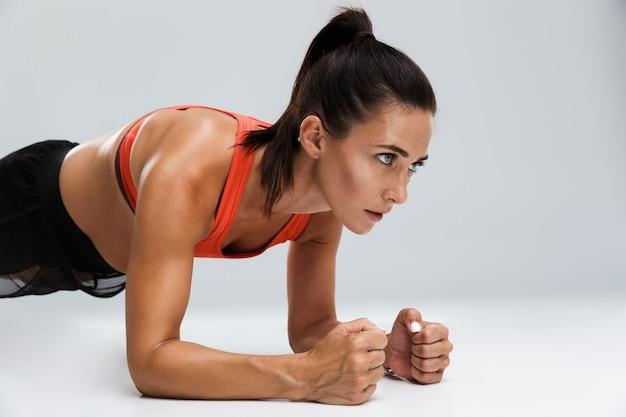 Mulher de esportes faz exercícios de esporte isolados dentro de casa.