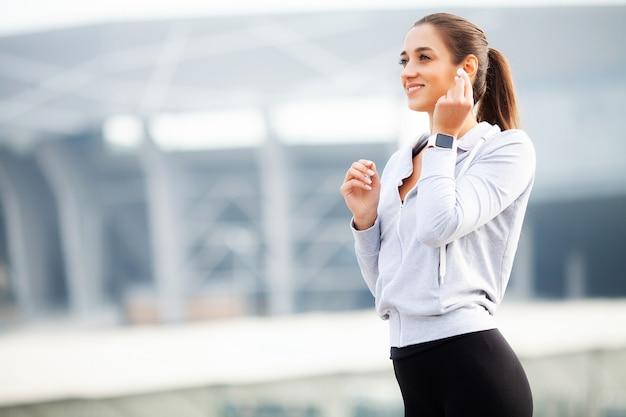 Mulher de esportes fazendo exercícios e ouvindo música no ambiente urbano