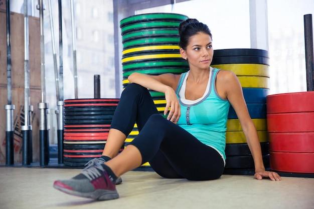 Mulher de esportes feliz sentada no chão na academia olhando para longe