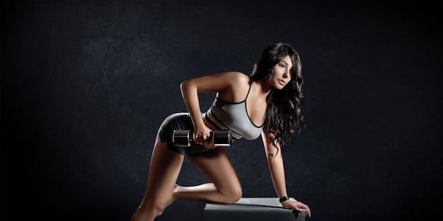 Mulher de esportes fitness treina em um fundo escuro