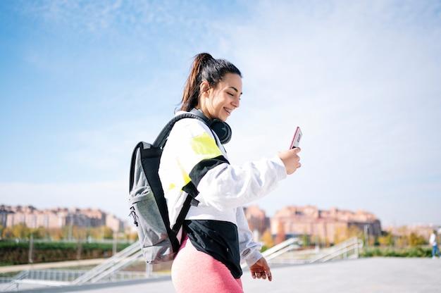 Mulher de esportes ouvindo música com fones de ouvido andando na rua