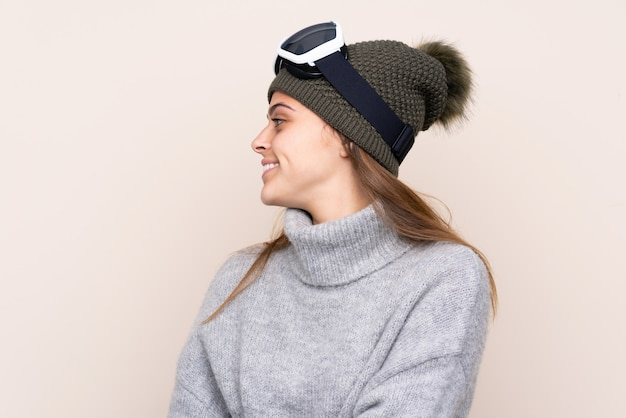 Mulher de esquiador adolescente com óculos de snowboard sobre parede isolada, olhando de lado