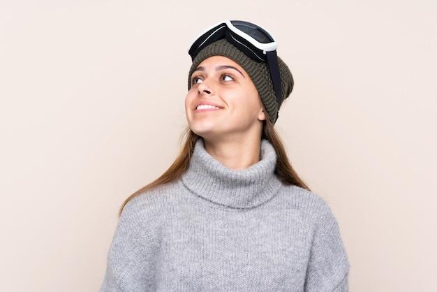 Mulher de esquiador adolescente com óculos de snowboard sobre parede isolada, olhando para cima enquanto sorrindo