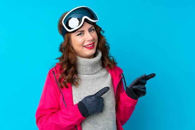 Mulher de esquiador com óculos de snowboard sobre parede azul isolada, apontando o dedo para o lado