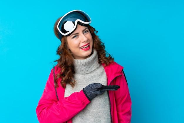 Mulher de esquiador com óculos de snowboard sobre parede azul isolada, estendendo as mãos para o lado para convidar para vir