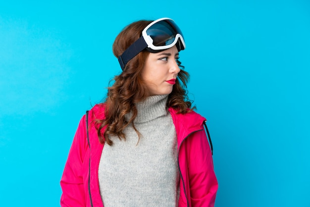Mulher de esquiador com óculos de snowboard sobre parede azul isolada, olhando de lado
