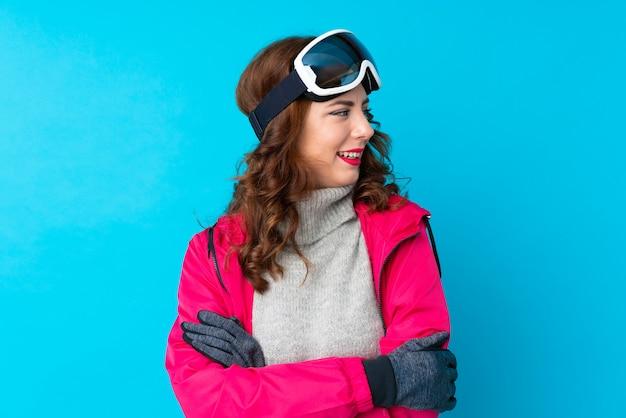 Mulher de esquiador com óculos de snowboard sobre parede azul isolada, olhando para o lado