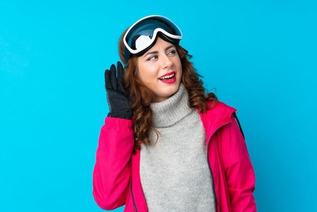 Mulher de esquiador com óculos de snowboard sobre parede azul isolada, ouvindo algo