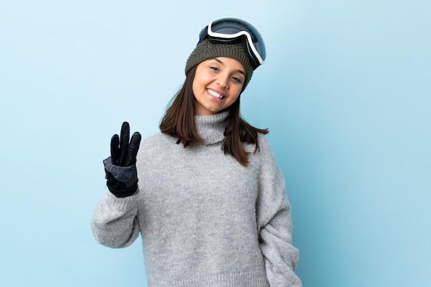 Mulher de esquiador de raça mista com óculos de snowboard sobre espaço azul isolado feliz e contando três com os dedos