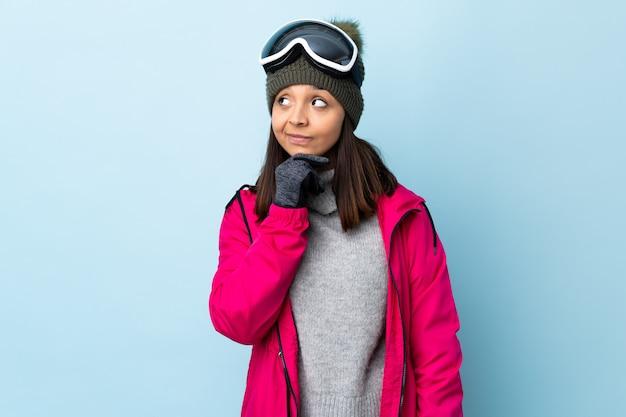 Mulher de esquiador de raça mista com óculos de snowboard sobre espaço azul isolado, pensando em uma idéia enquanto olha para cima
