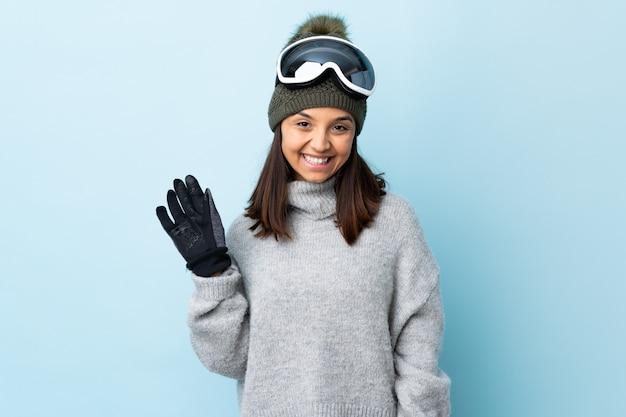 Mulher de esquiador de raça mista com óculos de snowboard sobre espaço azul isolado, saudando com mão com expressão feliz