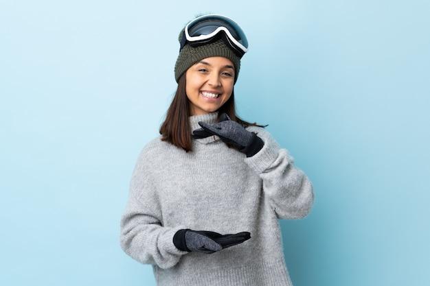Mulher de esquiador de raça mista com óculos de snowboard sobre espaço azul isolado segurando copyspace imaginário na palma da mão para inserir um anúncio