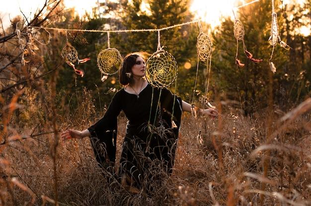 Mulher de estilo boho dançando perto de apanhadores de sonhos. liberdade feminina, bruxa, conceito de estilo cigano