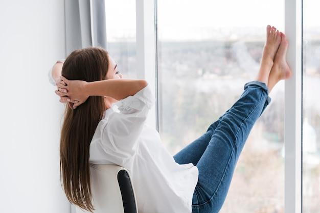 Mulher de estilo de vida em casa, olhando pela janela