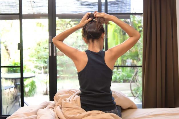 Mulher de estilo de vida em casa relaxante yoga na cama no quarto