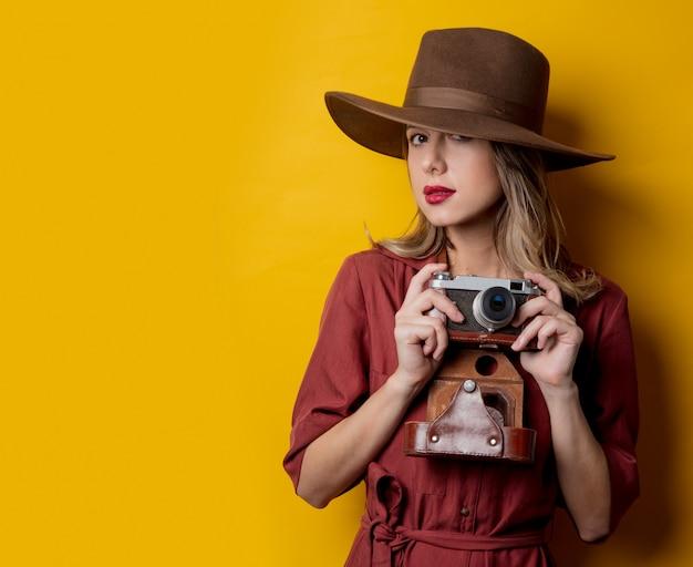 Mulher de estilo no chapéu com câmera vintage