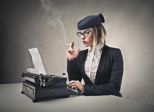 Mulher de estilo vintage e uma máquina de escrever