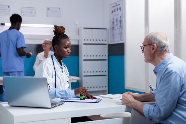 Mulher de etnia africana trabalhando como médica discutindo