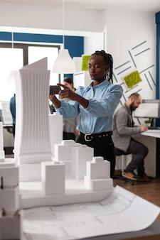 Mulher de etnia afro-americana trabalhando como arquiteta com planos de construção