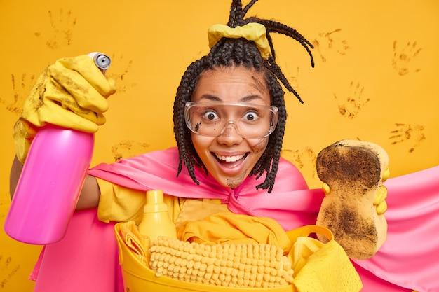 Mulher de etnia positiva vestida com fantasia de super-herói segura detergente de limpeza e a esponja suja sorri alegremente usando óculos de proteção transparentes, luvas de borracha. supermulher faz procedimentos de higiene