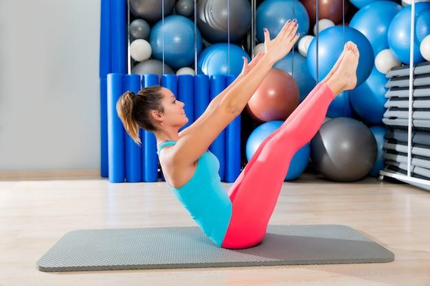 Mulher de exercício de provocação de pilates na esteira ginásio interior