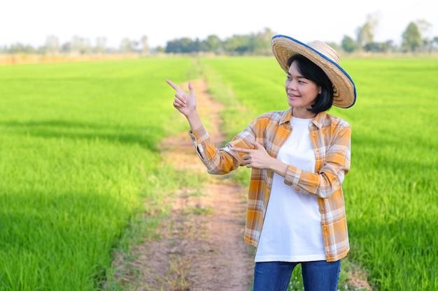 Mulher de fazendeiro asiático com as mãos levantadas apontam para o lado da imagem com espaço de cópia.