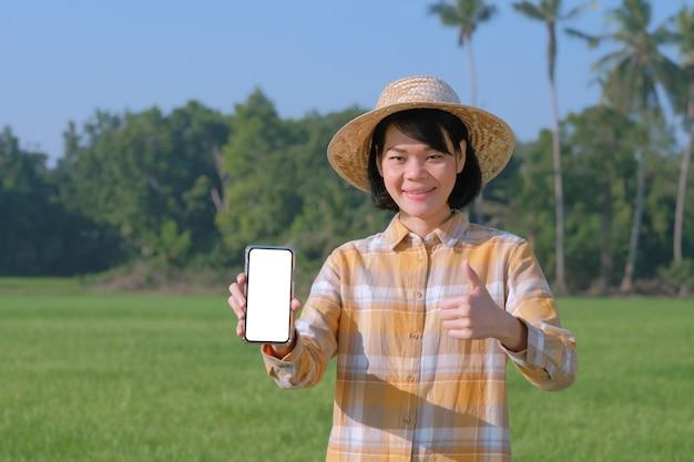 Mulher de fazendeiro asiático pose mostra tela do smartphone e polegar para cima na fazenda verde