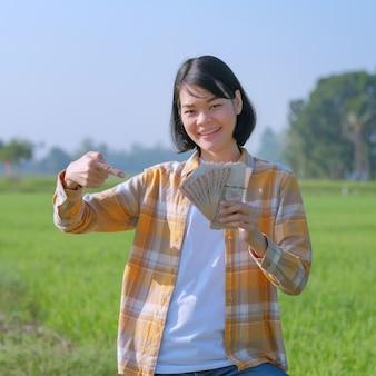 Mulher de fazendeiro asiático segurando o dinheiro da nota tailandesa e pose de dedo apontando para o dinheiro na fazenda de arroz verde