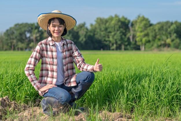 Mulher de fazendeiro asiático sentada e polegar para cima em uma fazenda de arroz verde