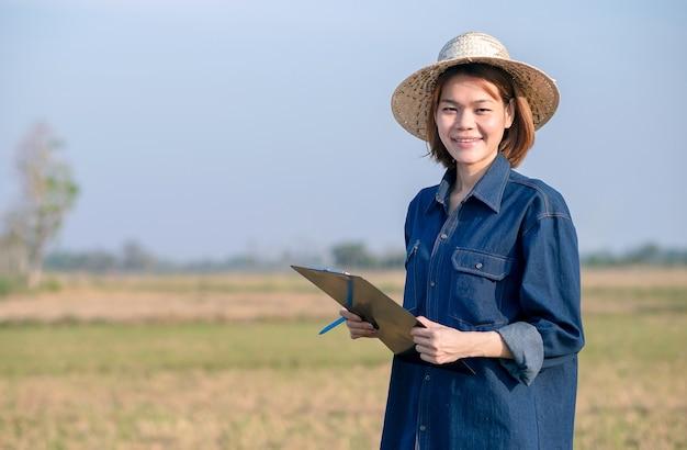 Mulher de fazendeiro asiático vestindo jeans segurando um bloco de notas e sorrindo em um campo