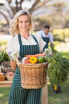 Mulher de fazendeiro sorridente segurando uma cesta de vegetal