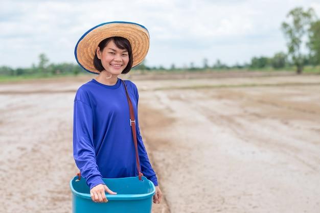 Mulher de fazendeiro tailandês segurando balde azul contendo semente de arroz em pé e sorriso