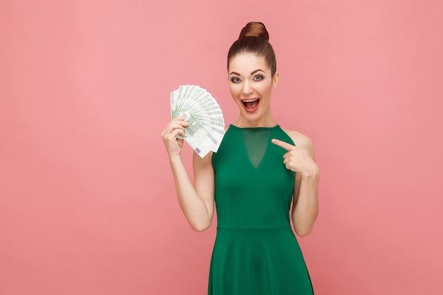 Mulher de felicidade segurando muitos euros e apontando o dedo. conceito de emoção e sentimentos de expressão. foto de estúdio, isolada em fundo rosa