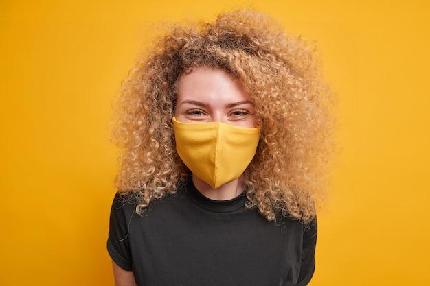 Mulher de feno encaracolada satisfeita usa máscara protetora para evitar a propagação do coronavírus vestida com camiseta preta casual expressa emoções positivas isoladas sobre a parede amarela tempo de quarentena