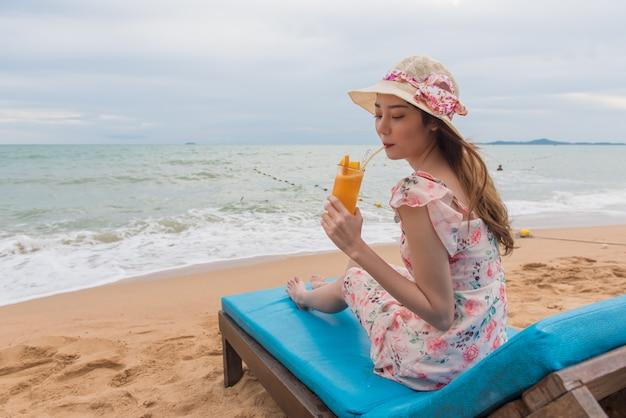 Mulher de férias de praia bebendo suco de laranja se divertindo na praia.