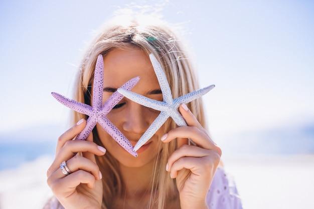 Mulher de férias segurando uma estrela do mar